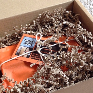 Gem's Concrete Gems product packaged in orange tissue paper in cardboard postage box